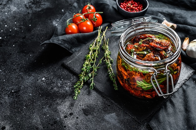 Sun dried tomatoes with herbs and salt in olive oil in a glass. top view. copy space