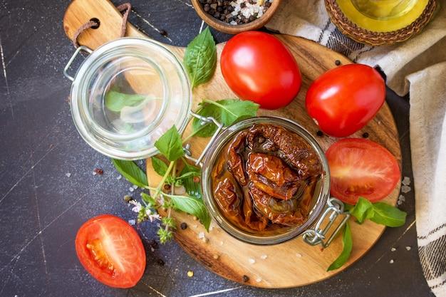 黒い石またはコンクリートのテーブルの上の瓶にオリーブオイルとサンドライトマト上面図フラットレイ