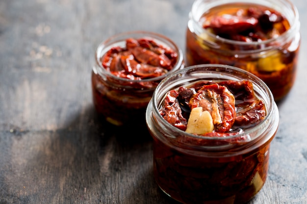 Sun dried tomatoes with olive oil in a jar on wood