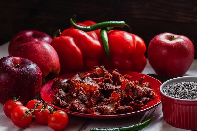 빨간 접시에 파프리카와 쌀쌀한 고추와 햇볕에 말린 토마토