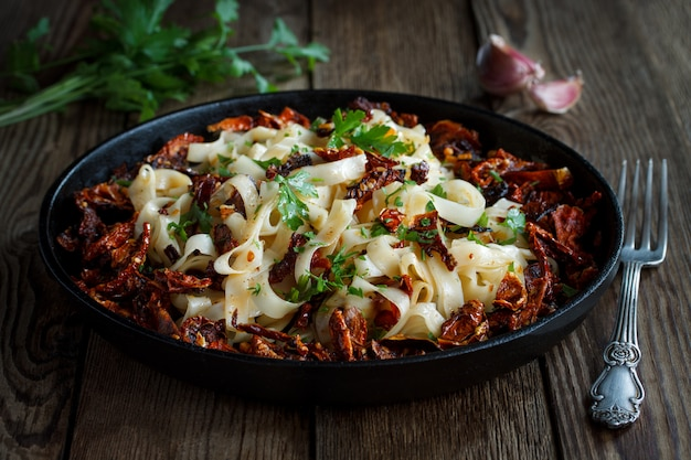 Sun-dried tomatoes with pasta, garlic and parsley in an iron black pan on a wooden table.