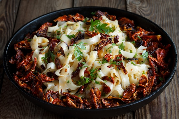 Sun-dried tomatoes with pasta, parsley in an iron black pan on a natural wooden . close up