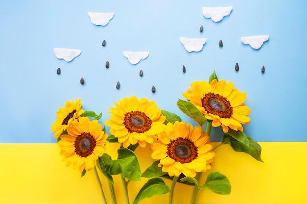 綿雲とウクライナの旗の上に分離された種子と太陽の花。黄色と青の背景に明るい小さなヒマワリ。