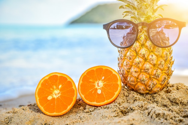 Sun glass is on pineapple at beach sea view background,summer holiday concept