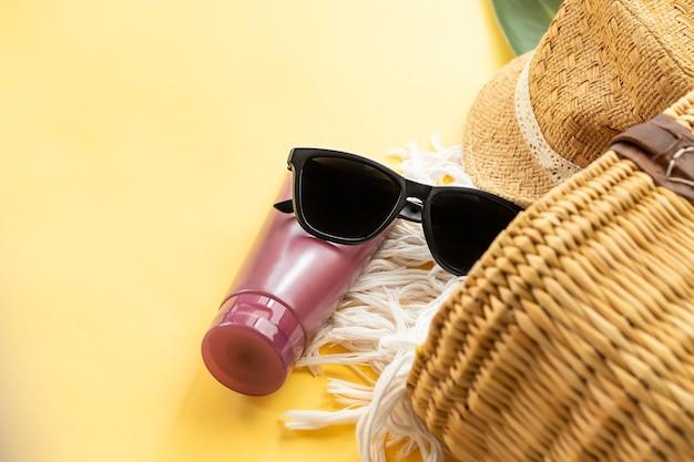 노란색 벽에 선 안경 선크림 크림과 짚 비치 가방