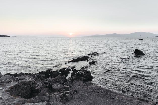 太陽は海に沈み、その前に黒い岩が