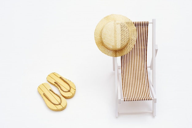 Sun hat on sunbed and pair of sandals on sandy beach