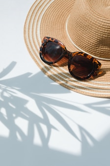 Sun hat and sunglasses with palm tree shadow