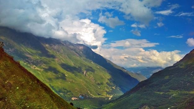 The sun illuminates the big green mountains