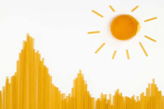 산에서 태양입니다. 언덕 모양의 익히지 않은 스파게티와 태양을 닮은 달걀. 여행 간식 개념입니다. 격리 된 흰색 배경입니다. 이탈리아 파스타 상위 뷰의 무리, 평평한 누워.