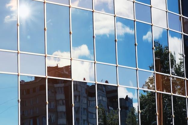 유리 사무실 건물에 태양 빛 하늘 구름 반사