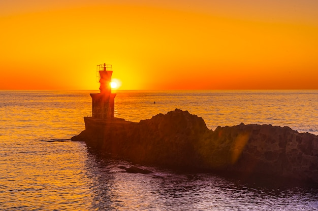 The sun behind the lighthouse at sunset in the town of pasajes san juan. gipuzkoa, basque country