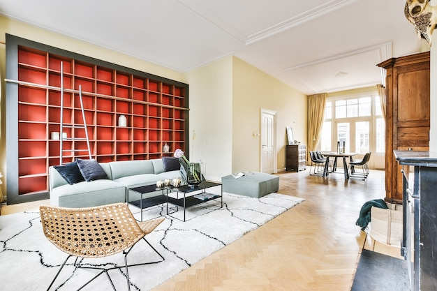 Sun lit living room with big windows and gray couch with carpet against red book shelves