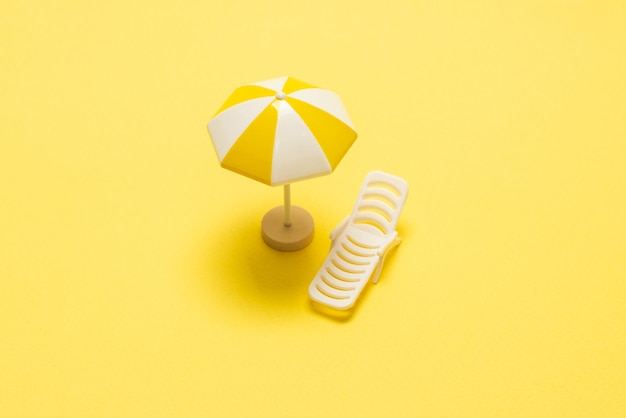Шезлонг и желтый зонтик на желтом фоне.