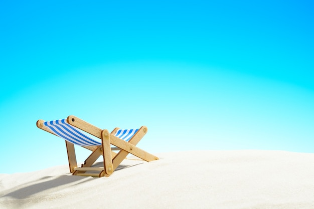 복사 공간이 있는 하늘과 모래 해변의 일광욕용 라운저