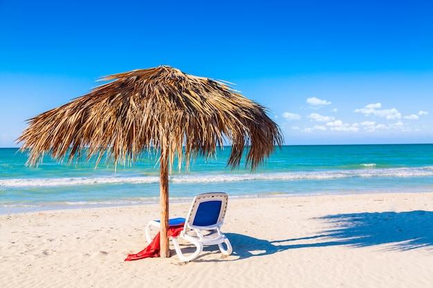 Шезлонг под зонтиком на песчаном пляже у моря и неба.