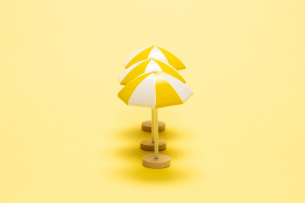 Sun lounger and yellow umbrella on a yellow background.