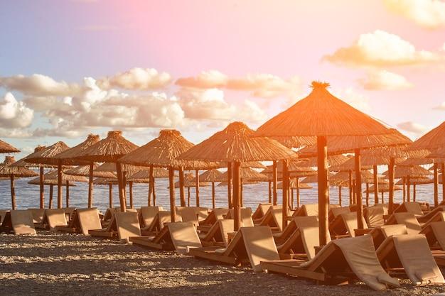 몬테네그로 부드바 해변에 일광욕용 라운저와 파라솔이 있습니다. 유럽. 여행기. 태양 플레어