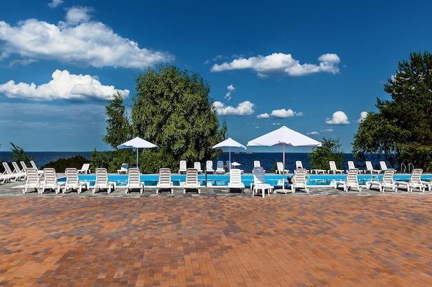 바다 옆 수영장 근처에 일광욕용 라운저와 파라솔이 있습니다. 농촌 휴가 단지의 외관입니다.