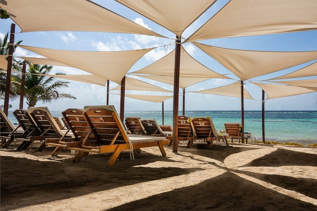 Sun loungers put next to each other under umbrellas on the beach