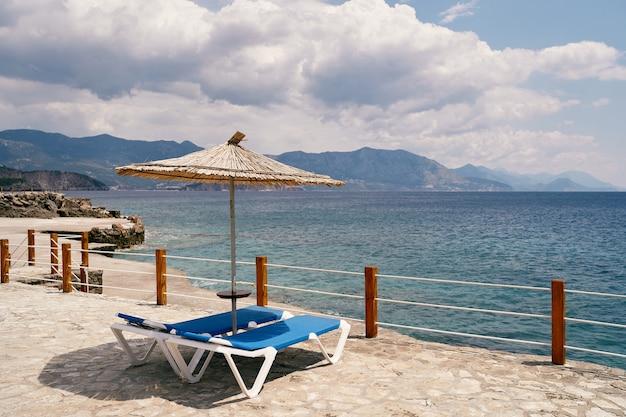 일광욕용 라운저는 바다가 내려다보이는 울타리 뒤에 있는 자갈이 깔린 해변의 우산 아래 서 있습니다.