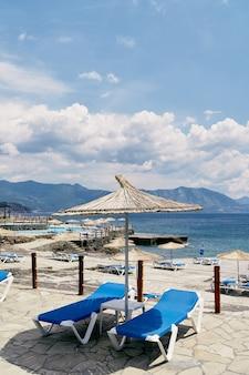 밀짚 우산 아래 일광욕용 긴 의자는 바다 근처의 포장 돌에 서 있다