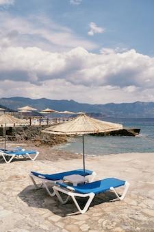 자갈이 깔린 해변의 파라솔 아래 테이블이 있는 일광욕용 라운저 프리미엄 사진