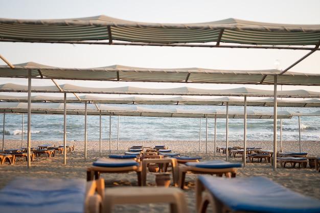 해변에 우산이 있는 일광욕용 긴 의자. 관광 산업. 고품질 사진