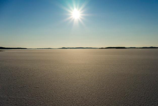冬の凍った湖の上の太陽