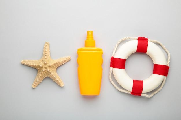 Бутылка защиты от солнца с пляжными аксессуарами на сером фоне. вид сверху.