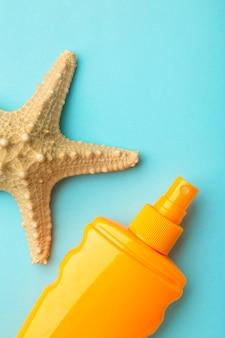 Бутылка защиты от солнца с морской звездой на синем фоне.