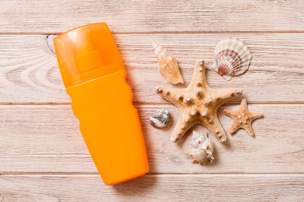 Sun protection cream bottle and seashells on wooden background. flat lay concept of summer travel vacation.