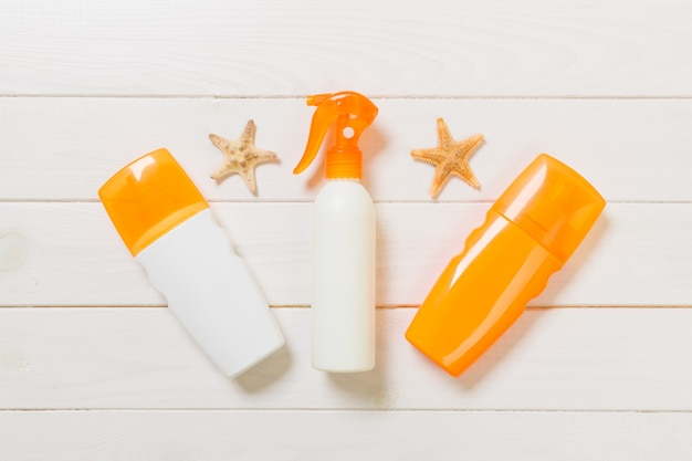 Sun protection cream bottles with seashells on white wooden table with copy space. travel healthcare accessories top view.