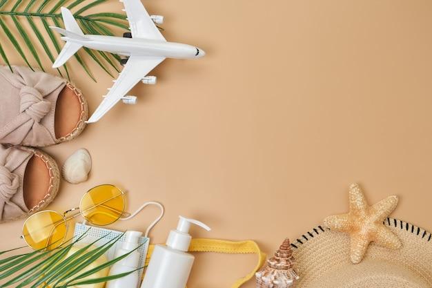 日焼け止めクリーム、サングラス、貝殻とヒトデ、夏の靴とサージカルマスクとベージュの砂の表面の飛行機