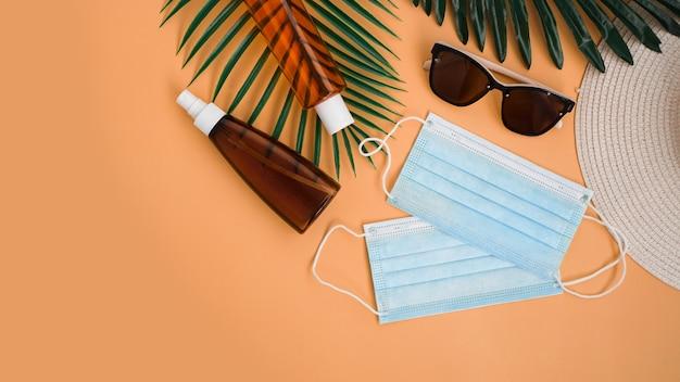 Защита от солнца. соломенная пляжная шляпа, солнцезащитные очки, защитный крем spf, медицинская маска. пляжный аксессуар. летнее путешествие в концепции карантина от коронавируса