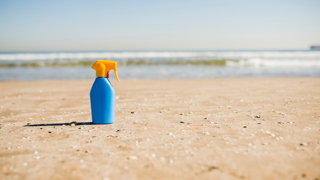 Sun protection and suntan cosmetics bottle on sand at beach
