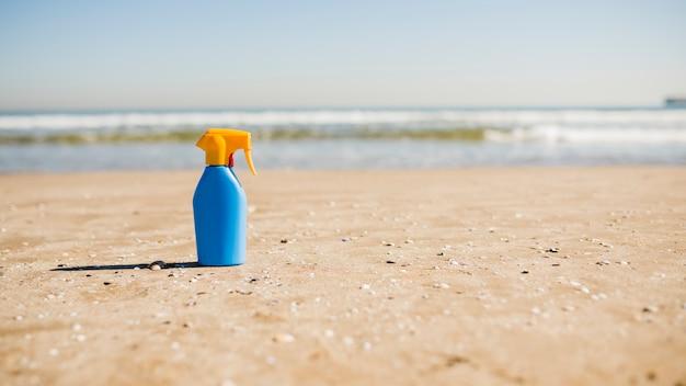 Sun protection and suntan cosmetics bottle on sand at beach