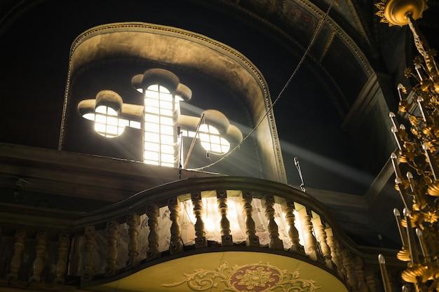 Солнечные лучи сияют через старое стеклянное окно церкви