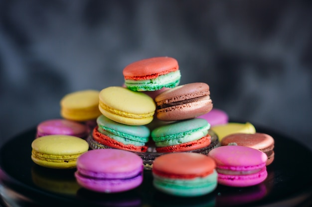 Sun rays lie over colorful macaroons on glass plate