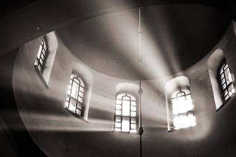 Sun rays make their way through the high vaulted arched window
