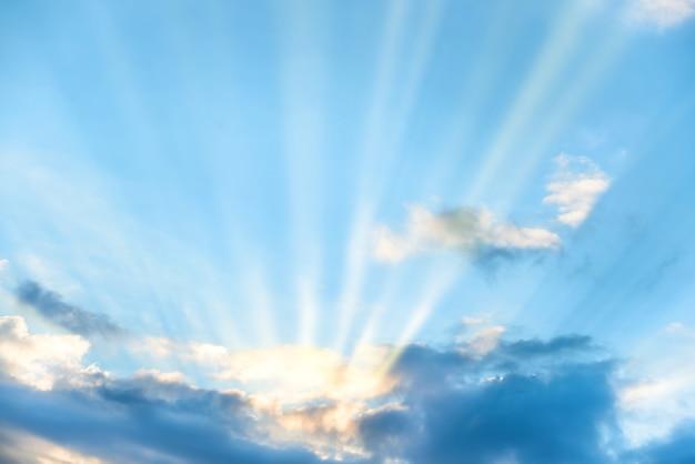 푸른 일몰 하늘에 구름을 통해 빛나는 태양 광선