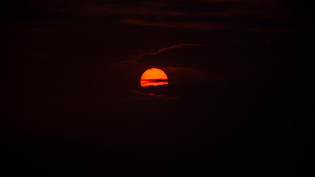 The sun rises behind the clouds in the early morning, photo have some noise and grain.