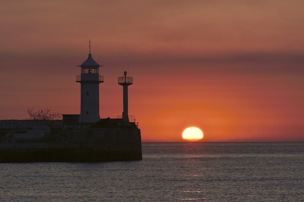 The sun rises from the horizon above the surface of the black sea in yalta