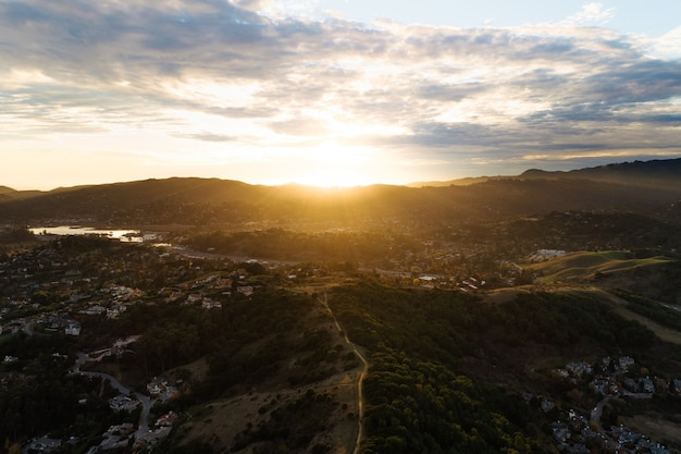 田園地帯の山岳風景に昇る朝日