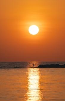 Sun above the sea on orange sky. fisherman with fishing rod on the rock.