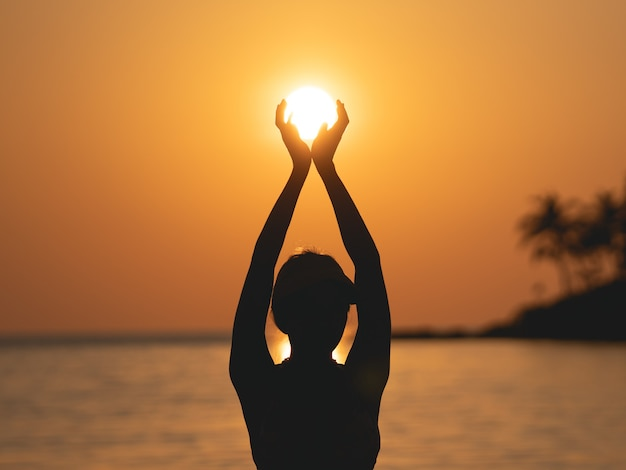 Sun above the sea on orange sky. woman standing on beach holding sun in her hands.