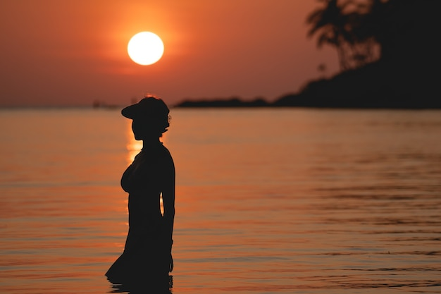 Sun above the sea on orange sky. woman standing on beach.