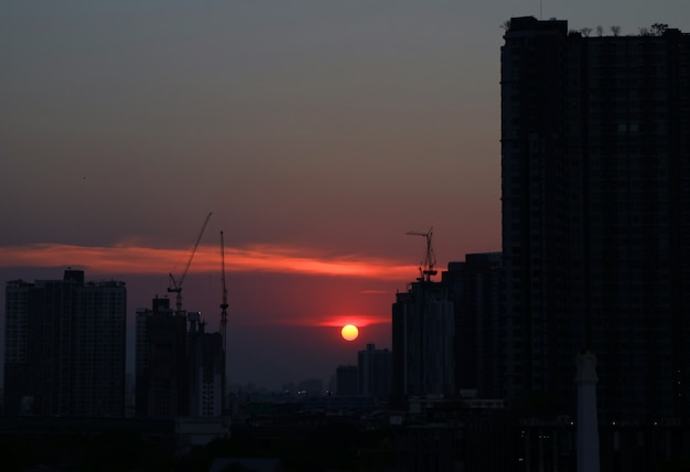 The sun setting amongst the skyscraper and construction buildings of bangkok, thailand