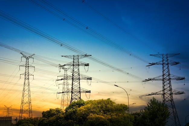 Солнце за силуэт электрических пилонов