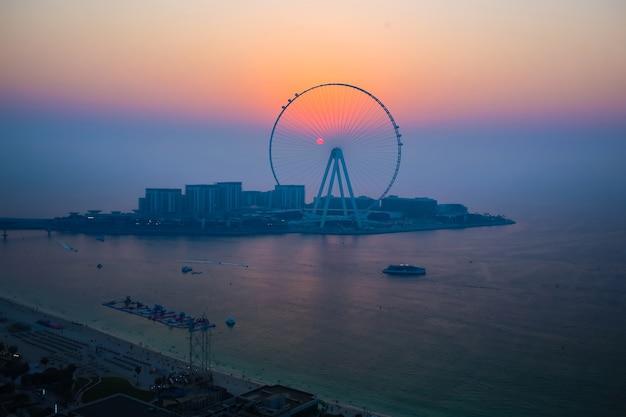 Sun setting behind dubai eye ferris observation wheel, scenic arabian sunset